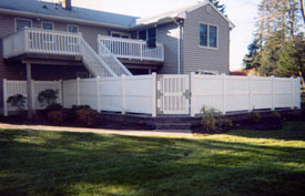 Vinyl fence, stone patio, and stone wall.