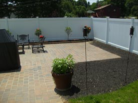 Stone patio and tall vinyl fence.