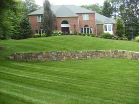 Beautiful lawn maintenance and stone wall.